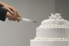 Detail of couple`s hands cutting wedding cake Royalty Free Stock Image