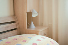 Detail of cozy bedroom. Table with pillow, reading lamp on bedside table made of wood. Unicolor curtain in the background. Pleasant warm atmosphere of home royalty free stock photos