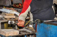 Detail of craftsman hands working on glass sculpture in a Murano workshop. Royalty Free Stock Photo