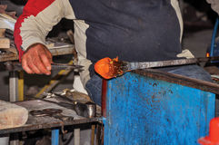 Detail of craftsman hands working on glass sculpture in a Murano workshop. Royalty Free Stock Photography