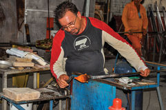 Detail of craftsman working on glass sculpture in a Murano workshop. Royalty Free Stock Photo