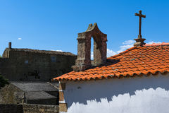 Detail of a cross and bell tower of a church in the historical village of Castelo Mendo Royalty Free Stock Images