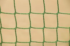 Detail of crossed  green soccer nets, soccer football in goal net with natural grass on football playground in the background Royalty Free Stock Images