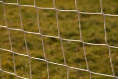Detail of crossed soccer nets, soccer football in goal net with natural grass on football playground in the background Stock Image