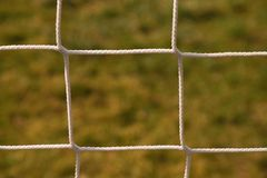 Detail of crossed soccer nets, soccer football in goal net with natural grass on football playground in the background Stock Images