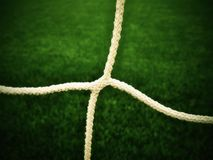 Detail of crossed soccer nets, soccer football in goal net with plastic grass on football playground in the background Stock Image
