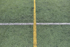 Detail of crossed yellow and white lines on football playground. Stock Images