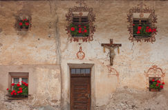 Detail of a crucifix and traditional old balconies with red geraniums from an old house in St. Magdalena in Val di Funes Stock Photos