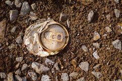Crushed aluminium can. Detail of crushed aluminium can left on rocky soil Royalty Free Stock Image