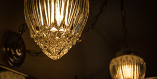 Detail of a crystal style glass cover which adorns a hanging chain link, swag style lamp in a bathroom. Royalty Free Stock Images