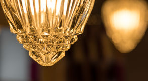 Detail of a crystal style glass cover which adorns a hanging chain link, swag style lamp. Royalty Free Stock Image