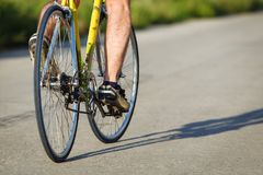 Detail of cyclist man feet riding bike on road. Horizontally framed shot stock photo