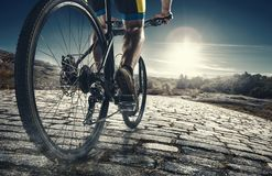 Detail of cyclist man feet riding mountain bike on outdoor trail on country road. In the evening time. Brick road. Close up of a bicycle. Helathy lifestyle stock photo