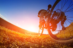 Detail of cyclist man feet riding mountain bike on outdoor trail in sunny meadow. Detail of the bicycle. Wheel. Legs and hand. Sunset. Low angle and fisheye Stock Photos