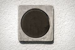 Detail of a dark square switch on a white wall. Of the small house Stock Images