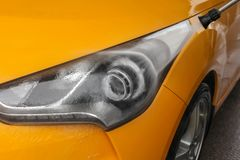 Detail on dark yellow car front light being washed with jet wate. R in carwash Royalty Free Stock Photo