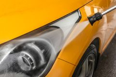 Detail on dark yellow car front light being washed with jet wate. R spray in carwash Royalty Free Stock Photo