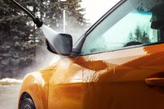 Detail on dark yellow car front mirror being washed with jet water stream in carwash. stock photo