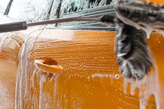 Detail of dark yellow car side washed in carwash. Brush leaving. Strokes in white soap and shampoo foam Stock Photo