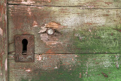 Detail of decaying wooden door. Screw and keyhole on dilapidated wooden door with surface of green peeling paint Royalty Free Stock Photos