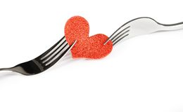 Detail of decorative red heart near forks on white background, valentine day dinner on white background