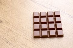 Delicious chocolate bar on wooden table. Detail of delicious chocolate bar on wooden table Stock Image