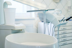 Detail of a dental surgery. Dental surgery with spittoon and plastic glass in foreground Royalty Free Stock Images