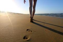 Detail der Beine der womenÂs gehend auf den sandigen Strand Stockfotografie