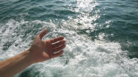 Detail der Hand der jungen Frau durch die Wasseroberfläche, die waterdrops spritzt und Wellen im haarscharfen Meer macht Langsame stock video