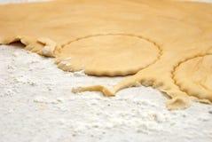 Detail der Kreise, die von einem Blatt des frischen Gebäcks geschnitten werden Stockbilder