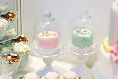 Detail der süßen Tabelle auf Hochzeit mit kleinen Kuchen und Braut und gro lizenzfreie stockfotos