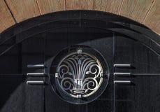 Detail des Außen-Art Deco-Baustilterrakottagebäudes mit Eingangsbogen und des Metallemblems auf schwarzem grainite lizenzfreies stockfoto