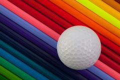 Detail des bunten Bleistifts und des Golfballs des Regenbogens auf dem Schreibtisch Lizenzfreies Stockbild