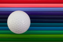 Detail des bunten Bleistifts und des Golfballs des Regenbogens auf dem Schreibtisch Lizenzfreie Stockbilder