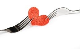 Detail des dekorativen roten Herzens nahe Gabeln auf weißem Hintergrund, Valentinstagabendessen auf weißem Hintergrund Lizenzfreies Stockfoto