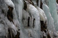 Detail des Eisfalles fließend hinunter den Abhang mit eindeutigem eingefroren Stockfotografie