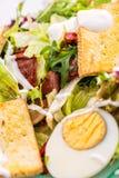 Detail des Frischgemüsesalats vom Arugula, vom Käse und von den Eiern auf Glasplatte auf weißem Hintergrund, Produktfotografie fü Stockfoto