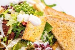 Detail des Frischgemüse Arugulasalats mit Käse, Eiern und Brotscheiben auf Glasplatte auf weißem Hintergrund, Produkt pH Lizenzfreie Stockbilder