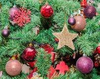 Detail des grünen Weihnachtsbaums mit farbigen Verzierungen, Kugeln, Sterne Stockfotos