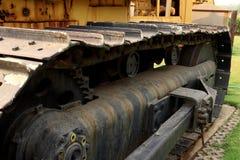 Detail des Raupenfahrwerks in der Baustelle mit Staub - quadratisches Foto der sofortigen Weinlese stockfotos