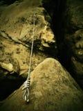 Detail des Stahlbolzen-Ankerauges und die Tampen, die in Sandstein verankert werden, schaukeln Bügeln Sie das verdrehte Seil, das Lizenzfreie Stockbilder