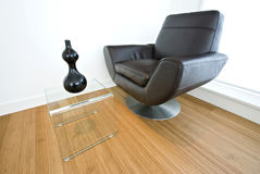 Detail of a designer leather armchair. With glass coffee table and decorative vase Stock Photos