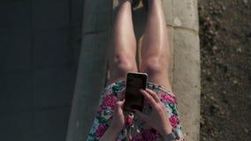 Detail dicht omhoog geschoten van een manier wijdde jonge vrouw gebruikend haar telefoon - het texting en overseinen - draagt gro stock footage