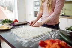 Detail die van vrouwelijke handen pizza van deeg maken Stock Foto