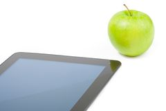 Detail of digital tablet pc near green apple on white background Royalty Free Stock Photo