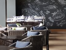 Detail of the dining room interior design at Holiday Inn hotel, Rayong. Rayong, Thailand - January 27th, 2018: View of the terrace dining area with tables laid Stock Photo