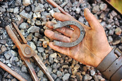 Detail of dirty hand holding horseshoe Stock Photography