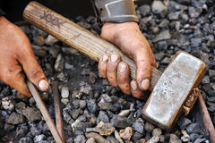 Detail of dirty hands holding hammer and rod Stock Photos