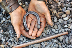 Detail of dirty hands holding horseshoe Stock Photos