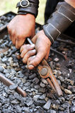 Detail of dirty hands holding pliers Royalty Free Stock Image